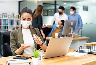 Asiatische Büroangestellte tragen Schutzmaske mit Alkoholtupfer für Hygiene  und Handdesinfektion im neuen Normalbüro