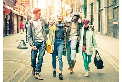 Fröhliche, multiethnische Freunde, die bei Shoreditch in London auf Brick Lane spazieren gehen