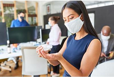Geschäftsfrau mit Gesichtsmaske im Büro, das die Hände desinfiziert, wegen Covid-19 und Corona-Virus