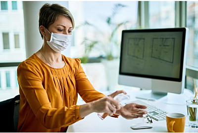 Geschäftsfrau mit Gesichtsmaske mit Handanisierer, während sie im Büro die Hände reinigt.