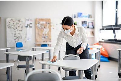 Lehrer zurück in der Schule nach Covid-19 Quarantäne und Absperrung, Desinfektion der Schreibtische.