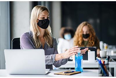 Junge Frau mit Gesichtsmaske zurück am Arbeitsplatz