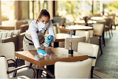 Junge Kellnerin, die Tische desinfiziert.jpg