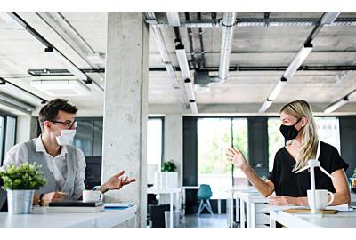 Junge Menschen mit Gesichtsmasken kehren nach der Schließung bei der Arbeit zurück.