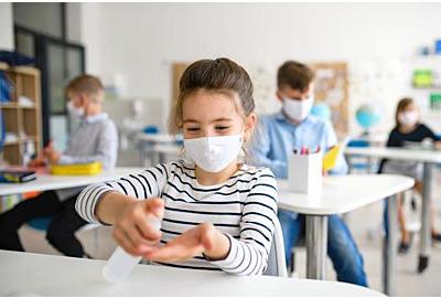 Hygienekonzept in Schulen: Kleines Mädchen mit Gesichtsmaske in der Schule nach Covid-19 Absperrung, Desinfektion der Hände.