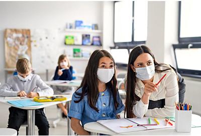Lehrer und Kinder mit Gesichtsmaske zurück in der Schule