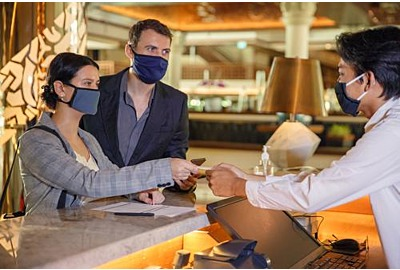 Mitarbeiter an der Rezeption im Hotel, der medizinische Maske  trägt.