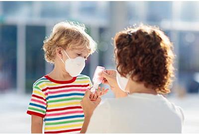 Zweite Corona-Welle: Mutter und Kind tragen Gesichtsmaske während des Ausbruchs von Coronavirus und Grippe