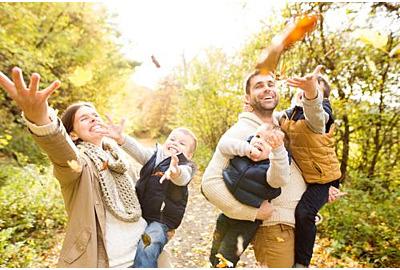 Schöne junge Familie auf einem Spaziergang im Herbstwald.
