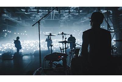 Musikgruppen Silhouette treten auf einer Konzertbühne auf. Silhouette des Schlagzeugers auf Schlagzeug Publikum, das Zigarettenanzünder und Mobiltelefone hält