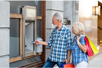 Senior couple with shopping bags using cash machine