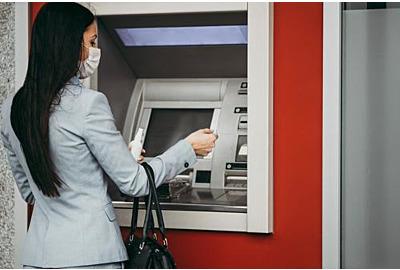 Elegante Geschäftsfrau mit Schutzmaske, die auf der Stadtstraße steht und Geldautomaten zum Abheben von Bargeld verwendet.