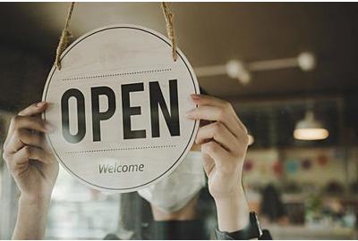 Öffnen. Barista, Kellnerin mit Schutzmaske, die an der Glastür in der modernen Café-Café-Café-Café-Bar, im Einzelhandel, in der Kleinfirma, im Konzept für Essen und Trinken auftritt