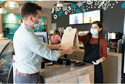 Mid-erwachsener Mann, der das Paket von weiblichen Mitarbeitern am Abnahtheken im Restaurant mitnimmt