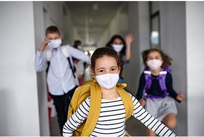 Gruppe fröhlicher Kinder, die nach Covid-19 Quarantäne und Schließung von der Schule nach Hause gehen.