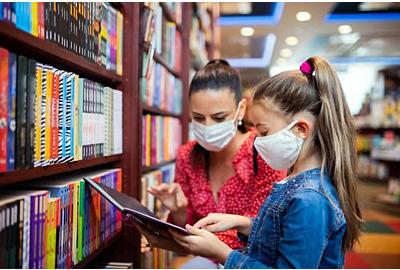Mutter und Tochter mit Gesichtsmaske Shopping in Buchhandlung, Coronavirus Konzept.