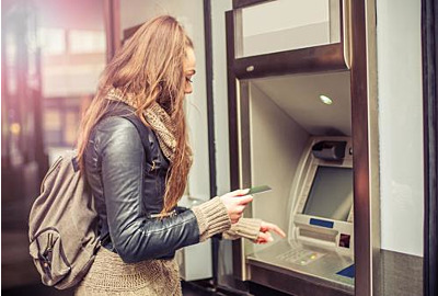 Junge Frau, die Geld von der Kreditkarte am ATM abzieht